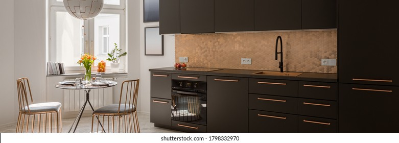 Panorama of modern kitchen with stylish black cupboards and drawers, copper hexagonal tiles and handles and with new black dining table and two, elegant copper chairs