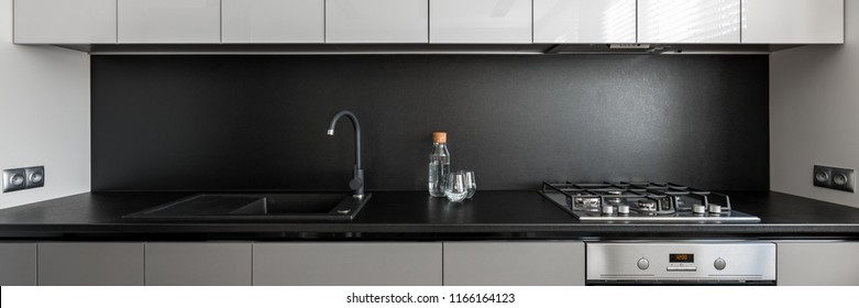 Panorama of modern kitchen unit with black worktop and backsplash