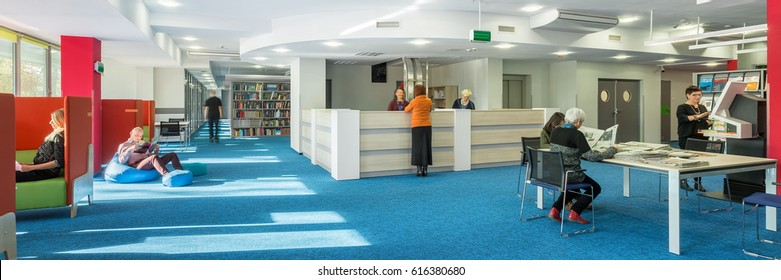 Panorama of modern and spacious university library with blue carpet on the floor