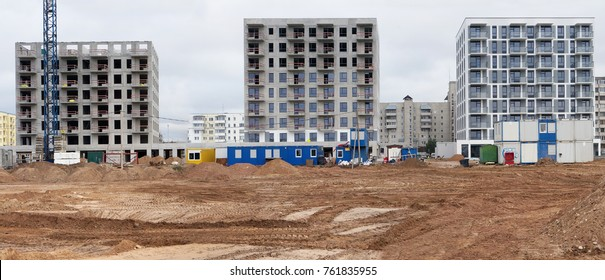 Panorama of a modern standard concrete houses buildings construction  in a small European city. No logos or trademarks,  Panoramic collage from several outdoor cloudy day photos