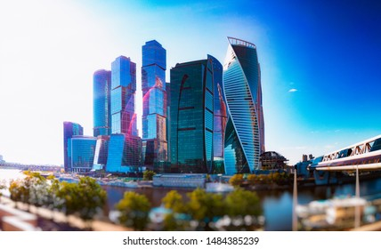 Panorama of Moscow City skyscrapers across the river against a background of clear blue sky and blurred foreground