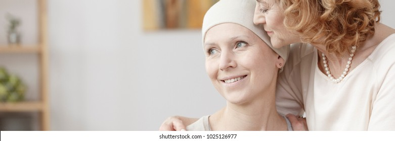 Panorama of mother hugging smiling sick woman during illness
