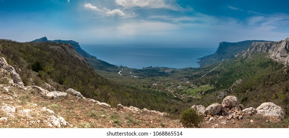 Panorama of the mountain Crimea tourism and outdoor activities in Russia: rocks and clouds, spring green grass and blue sky