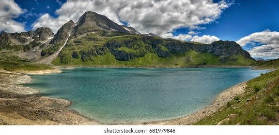 Panorama mountain lake of glacial origin in a beautiful summer day with clouds in the sky