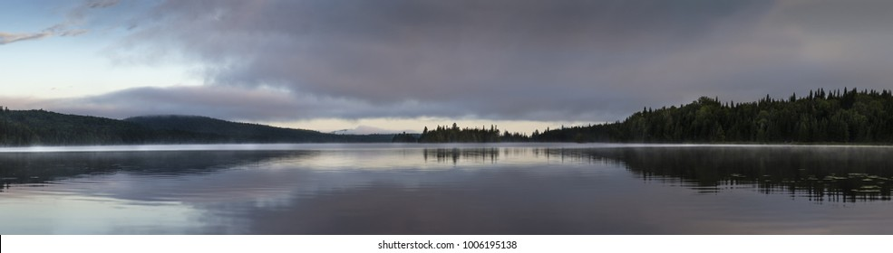 panorama of mountain lake Lac des Cypres in Mont-Tremblant provincial park at sunrise on foggy morning in North America, Canada, Quebec