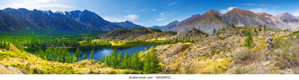 Panorama of a mountain landscape. Clear lake mirror water. Coniferous forest on rocky hills. Altai, Russia.