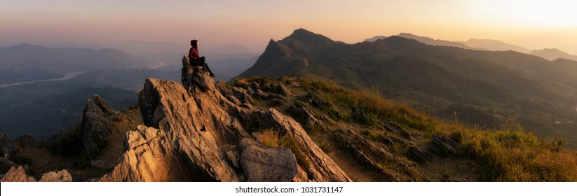 Panorama Mountain landscape with sunset on (Doi Pha Tang) viewpoint, Chiang Rai Thailand. Doi Pha Tang offers the best spot to watch the scenic Mekong river at the hilltop. Woman on top.