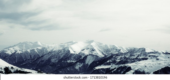 The panorama of a mountain range with mountain peaks and snow covered mountain slopes and a cloudy sky in black and white