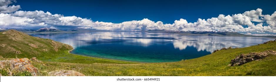 Panorama of mountain Son Kol lake. Beautiful clouds reflected in water. Kyrgyzstan.