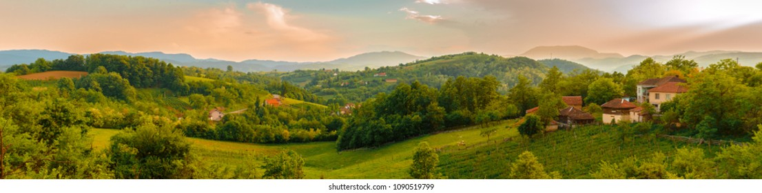 Panorama of mountain village at sunset. Valley in village Stubo, near town of Valjevo, at spring evening. Household with meadows and farmland. Western Serbia, mountain region. Europe.