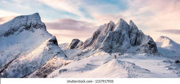 Panorama of Mountaineer standing on top of snowy mountain range at Senja, Norway