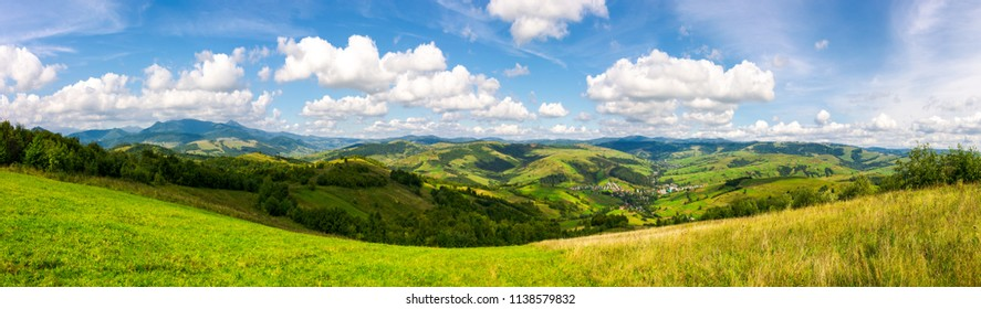 panorama of mountainous countryside. lovely countryside scenery in early autumn with grassy field on hillside, village down in the valley and clouds on a blue sky over the distant ridge