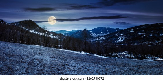 panorama of mountainous countryside in springtime at night in full moon light. leafless trees and weathered grass on a meadow. spots of snow on the forested hills