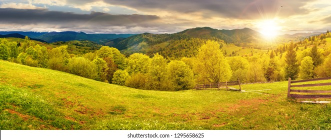 panorama of mountainous countryside in springtime at sunset. beautiful highland landscape. wooden fence on the grassy field. row of trees along the hill. rural area in the distance. cloudy sky