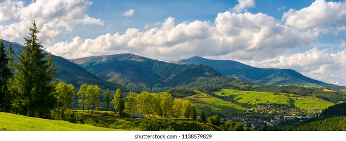 panorama of mountainous urban area. lovely countryside landscape in early autumn. trees along the road down the hill. village down in the valley and clouds on a blue sky over the distant ridge