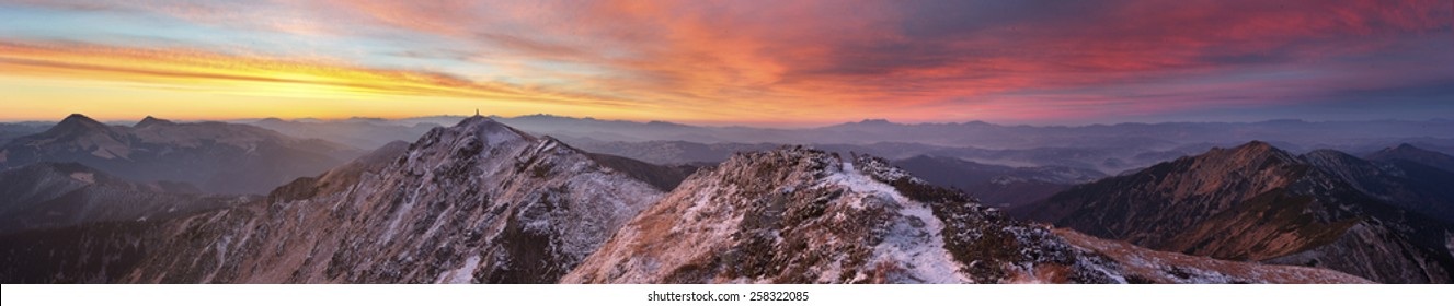 panorama of mountains covered with light snow. all lit yellow light of the sun. the sky beautiful red clouds