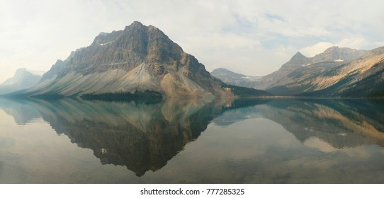 Panorama of the Mountains Reflected In Bow Lake Patially Obscured by Smoke and Clouds Alberta, Canada
