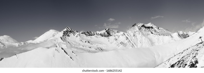 Panorama of mountains with snowy off-piste slope at winter. Caucasus Mountains, Georgia, region Gudauri. Black and white toned landscape.