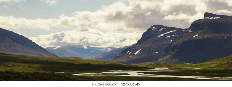 Panorama of mountains in a valley with a river flowing during the hike of Kungsleden (Kings path) in northern Sweden.
