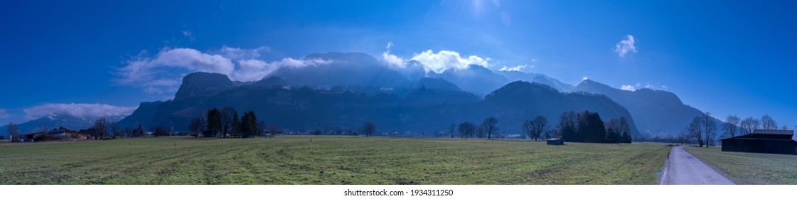 Panorama of the mountains of Vorarlberg as seen from the Rhine valley. Morning mist drifts over the mountains and shows the many structures of the mountain range. sunny morning with backlight. Austria