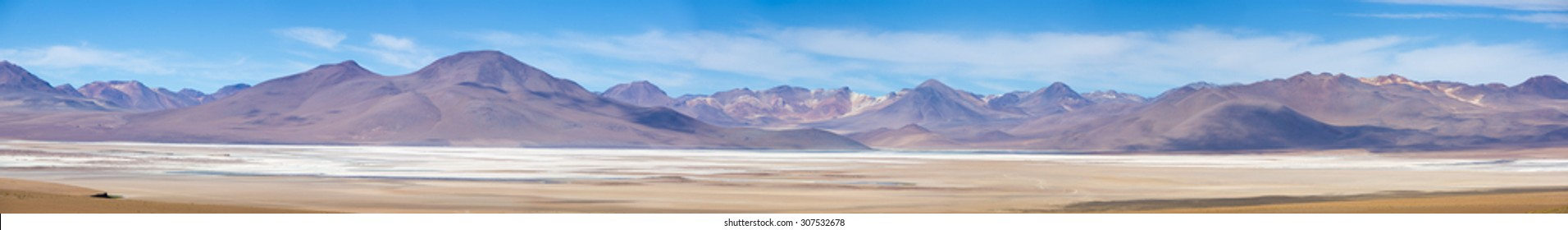 Panorama of mountains and white salt pan in Eduardo Avaroa Andean Fauna National Reserve against a clear blue sky, Bolivia