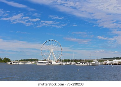 Panorama of National Harbor with Ferris and yachts at pier in Maryland, USA. National Harbor waterfront under blue skies with scenic clouds.