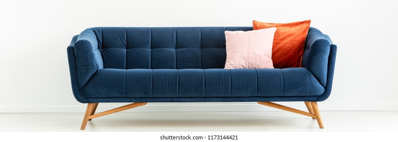 Panorama of navy blue settee with colorful cushions in white living room interior. Real photo