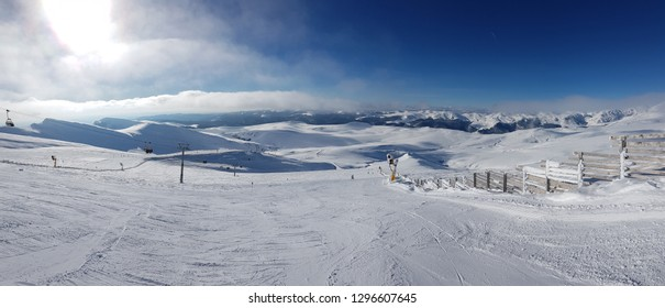 Panorama of nearly empty Carpathian mountains skiing slope in Sinaia, Romania, with ski lift