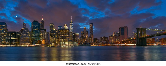 Panorama of New York City Brooklyn Bridge and Manhattan skyline with skyscrapers over Hudson River illuminated with lights at dusk after sunset,