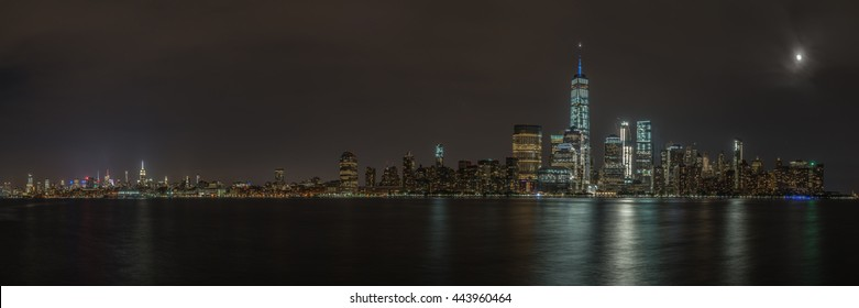 Panorama of New York City Skyline at night with the moon shining.