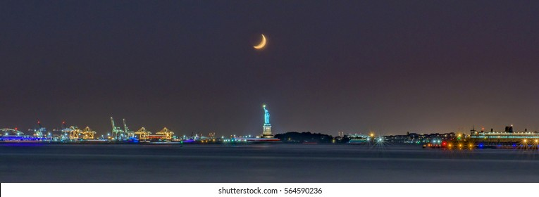 Panorama of New York harbor by night with a crescent moon over the Statue of Liberty