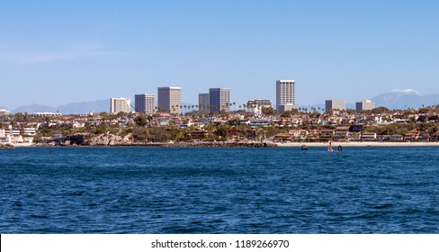panorama of Newport Beach California skyline, the entrance to the harbor, Corona Del Mar beach, Fashion Island shopping center,and snow capped San Gabriel mountains ghosting in the background