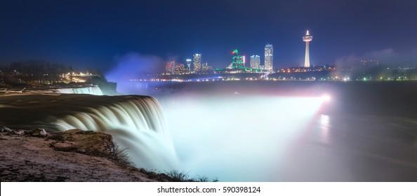 Panorama of Niagara falls with white lights shining at night