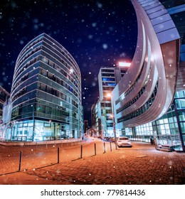 Panorama of the night city of Dusseldorf in winter during a snowstorm. Bokeh light effect, soft filter.