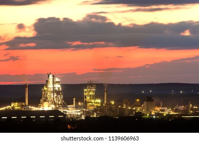 Panorama night view of brightly lit modern cement plant and power station in Ivano-Frankivsk, Ukraine under dramatic red sky on distant dark green hills background. Technology and ecological problems.
