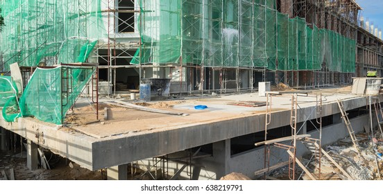 Panorama office and residential building under construction with safety net, green grid prevent object falling from height in Malacca, Malaysia. Scaffolding, formwork in installation, building fencing