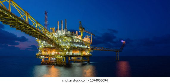 Panorama of offshore oil and gas construction platform in sun set where produced raw gases and crude for set to onshore refinery and petrochemical plant, Power and energy business industry.