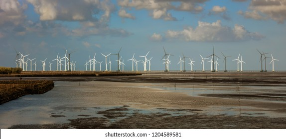 Panorama of Offshore Wind Turbines near Bac Lieu city in South Vietnam at low tide. Nha Mat village. Evening view