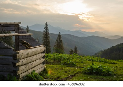 panorama of old demolished house on meadow with mountain sunset background