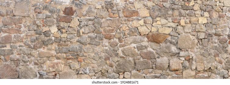 Panorama - Alte graubraune Mauer aus vielen verschiedenen Natursteinen in unregelmäßiger Anordnung