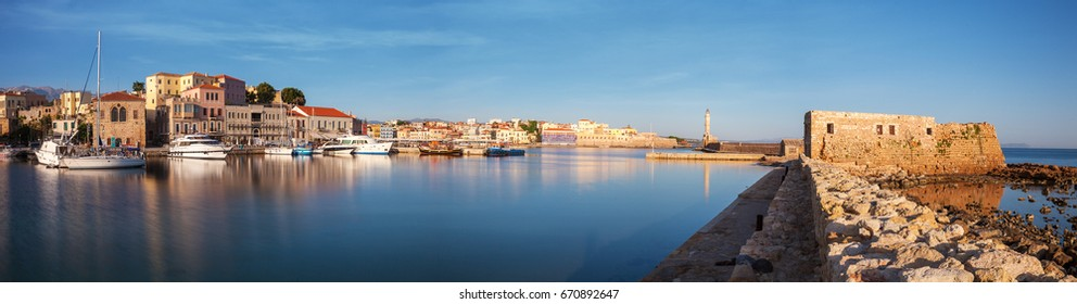 Panorama of Old harbor of Chania with the lighthouse and fortification at sunrise, Crete, Greece