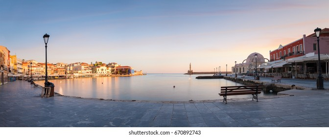 Panorama of Old harbor of Chania with the lighthouse, bench and lamp at sunrise, Crete, Greece