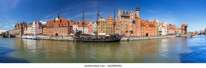Panorama of the old town in Gdansk with historical port crane reflected in Motlawa river, Poland