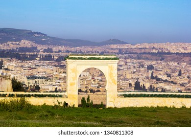 Panorama of the old town medina of Fes on the Borj Sud hill through an ancient gate on hazy morning, Morocco