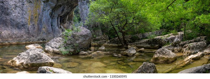 panorama on a scenery with a natural arch dug in the rock by a river