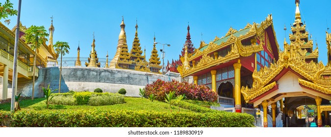 Panorama of ornamental flower bed on the slope of Singuttara Hill with the building of the Eastern stairway, roofs and tops of stupas of Shwedagon Zedi Daw, Yangon, Myanmar.