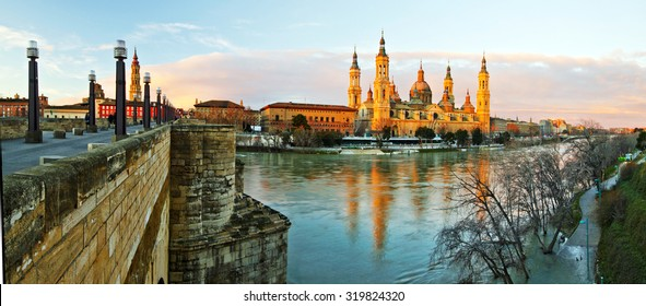 Panorama of ??Cathedral of Our Lady of Pillar Ebro river in early morning lights Zaragoza, High winter flow is flooding river birders. Cathedral of the Savior is at left behind the old stone bridge