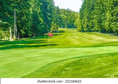 Panorama, outlook at the beautiful golf course with red flag in a sunny day. Canada, Vancouver.