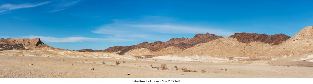 panorama of the outside of the south rim of the makhtesh ramon crater in israel including the israel national trail on ramon's tooth magmatic intrustion with wispy clouds in the background