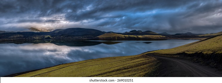 Panorama of overcast sky over mountains reflected in lake at daybreak with a winding road in the foreground, Landmannalaugar, Iceland.